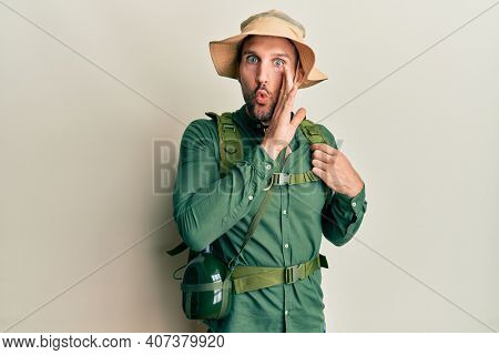 Handsome man with beard wearing explorer hat and backpack hand on mouth telling secret rumor, whispering malicious talk conversation