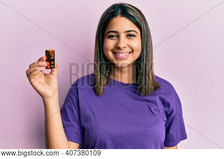 Young latin woman holding small gold ingot looking positive and happy standing and smiling with a confident smile showing teeth