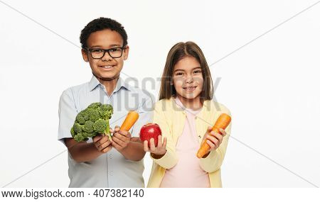 Latino Girl And African American Boy Are Holding Broccoli, Carrots, And An Apple. Benefits Of Vegeta