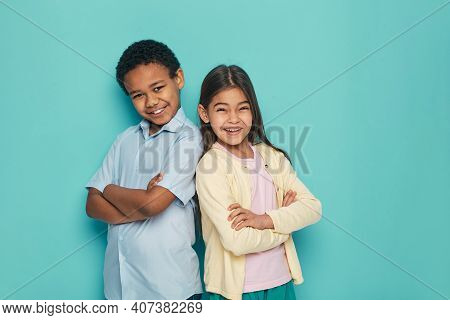 African American Boy And Latino Girl Standing Back To Back With Arms Crossed On A Turquoise Backgrou