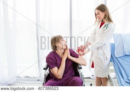 Doctor Giving A Gift Box To Patient In A Wheelchair.