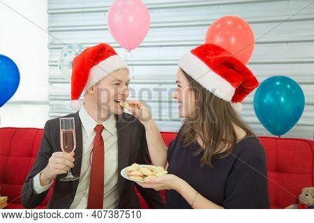 A Man And Woman Wearing A Christmas Hat Hold A Champagne Glass To Celebrate Xmas Day.
