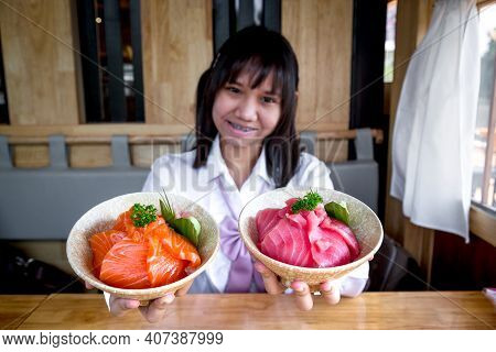 A Girl Teenage Shows A Salmon Don And Maguro Or Tuna Don In A Japanese Restaurant.