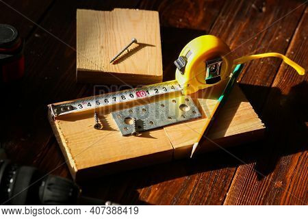 The Black Screw And Is Measured By A Yellow Tape Measure With A Ruler On A Wooden Board Background.
