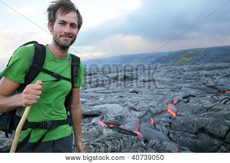 Hawaii hiker hiking by flowing lava from Kilauea volcano around Hawaii volcanoes national park, USA. Young caucasian man..