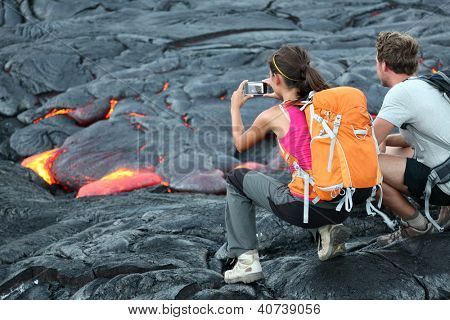 Hawaii lava tourist. Tourists taking photo of flowing lava from Kilauea volcano around Hawaii volcanoes national park, USA.