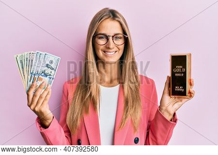 Young blonde woman wearing business style holding gold ingot and dollars smiling with a happy and cool smile on face. showing teeth.