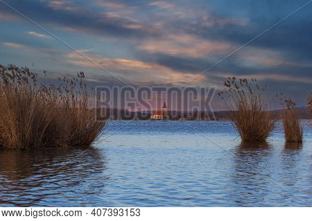 Lake Musov With The Church Of St. Linhart In The Czech Republic In Europe. There Is A Reed Around. I
