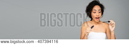 Amazed African American Woman Holding Mascara Isolated On Grey With Copy Space, Banner.