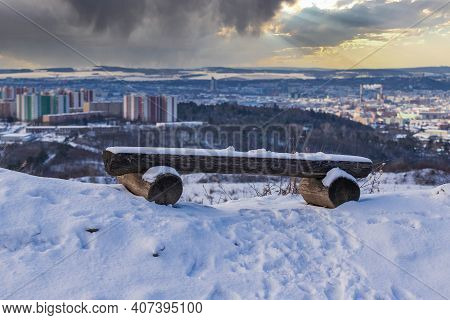 Wooden Bench In The Snow On Which Is A Layer Of White Snow. In The Background Is The City Of Brno In