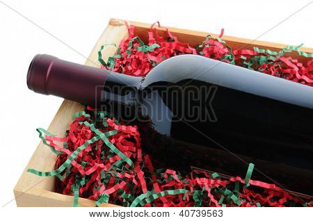 Closeup of a red wine bottle in a wood shipping crate with shredded filler paper in Christmas Holiday colors. Horizontal format isolated on a white background.