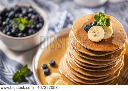 Stack of home baked blueberry pancakes with banana, maple syrup and mint