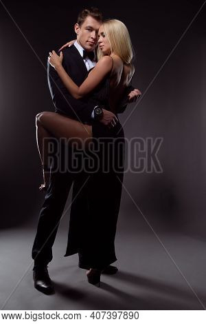 Gorgeous Couple In Love In Elegant Evening Dresses Passionately Embracing On A Dark Background