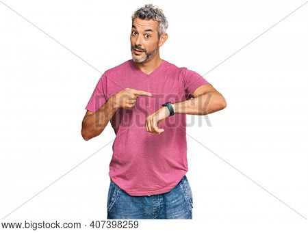 Middle age grey-haired man wearing casual clothes in hurry pointing to watch time, impatience, upset and angry for deadline delay
