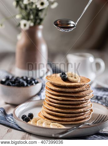 Stack Of Home Baked Banana Pancakes With Blueberries, Gravy Boat With Maple Syrup Hangs Over Pancake