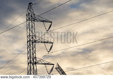 A Power Pole Built On The Basis Of A Truss Against The Sky And Clouds At Sunset.