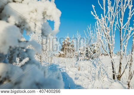 Winter Snow Covered Wooden Church View. Wooden Church In Winter Snow Forest Scene. Winter Church In