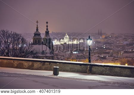 View Of Illuminated Street Against Snowy City At Night. Cityscape Of Prague In Winter, Czech Republi