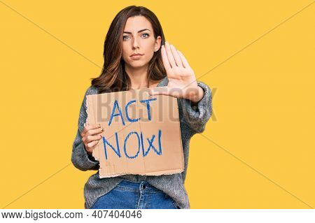 Young brunette woman holding act now banner with open hand doing stop sign with serious and confident expression, defense gesture