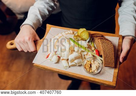 In A Beautiful Restaurant, A Waiter Brings A Ready-made Dish For A Young Guy Man In A Suit, On A Tra