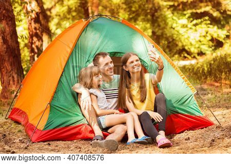 Young Happy Family With Smartphone Taking Selfie At Campsite. Smile Family Spend Active Time Outside