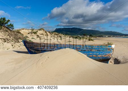 A Colorful Wreck Of An Old Wooden Rowboat Buried In The Sand On The Playa De Bolonia