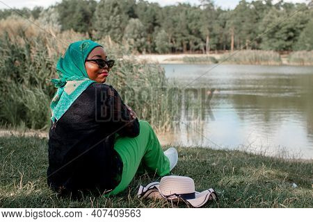 African Woman In Muslim Clothes Near Lake Enjoys The Beautiful Nature
