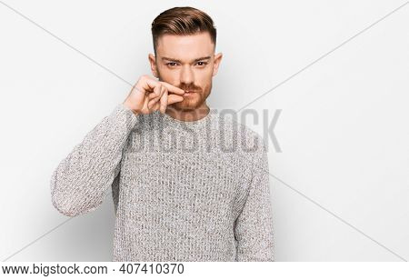 Young redhead man wearing casual winter sweater mouth and lips shut as zip with fingers. secret and silent, taboo talking