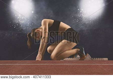 Woman sprinter leaving starting blocks on the athletic track. Matte image