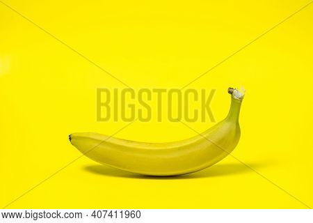 Banana On A Yellow Background. Fresh Yellow Banana. One Banana In The Center Of The Frame. Exotic Fr