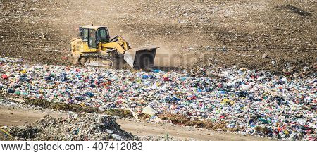 Yellow Tractor Works On Huge Landfill Of Big City. A Lot Of Garbage On Dump. Waste Sorting On Dumpin