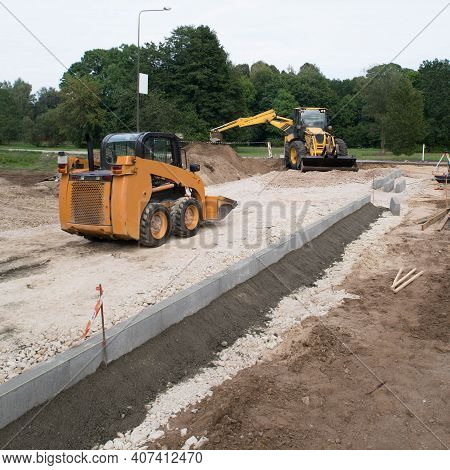 Construction Site Of New Sidewalk. Yellow Excavator. Road Roller. Skid Loader. Install Of Concrete C
