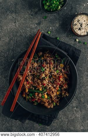 Fried Rice With Vegetables, Green Onion And Sesame In Black Bowl On Stone Background.