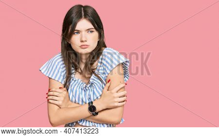 Young beautiful caucasian girl wearing casual clothes shaking and freezing for winter cold with sad and shock expression on face