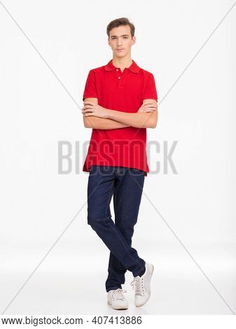 Photo of  young  confident man looking at camera. Full length Portrait of handsome guy with a calm emotions, posing at studio. Attractive male face. Teenager in a red shirt and blue jeans.