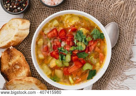 Minestrone Soup In A White Dish On Burlap Napkins, Top View. Italian Soup With Seasonal Vegetables,