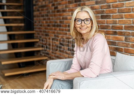 Portrait Of A Cheerful Mature Blonde Woman Sitting On The Chair And Smiling Against A Brick Wall Bac