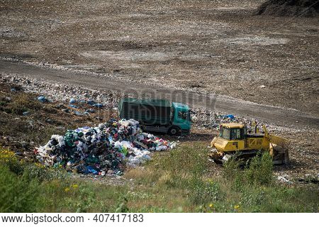 Huge Landfill Of Big City. Tractor And Truck On Dump. Household Garbage. Environment Pollution.