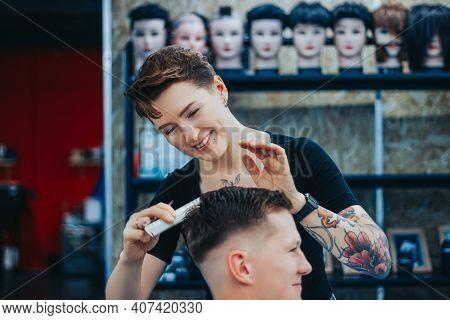 Minsk, Belarus - October 14, 2020: A Tattooed Woman Hairdresser Cuts Guys Hair
