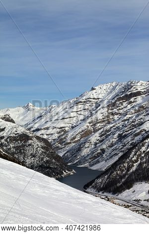 Off Piste Ski Slope, Snowy High Mountains With Forest, Big Lake And Blue Cloudy Sky At Winter. Itali