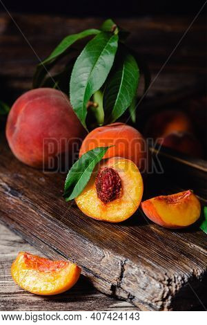 Juicy Ripe Peach On Dark Wooden Rustic Cutting Board. Delicious Farm Peaches With Leaves Whole Fruit