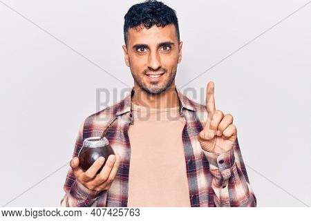 Young hispanic man drinking mate infusion smiling with an idea or question pointing finger with happy face, number one