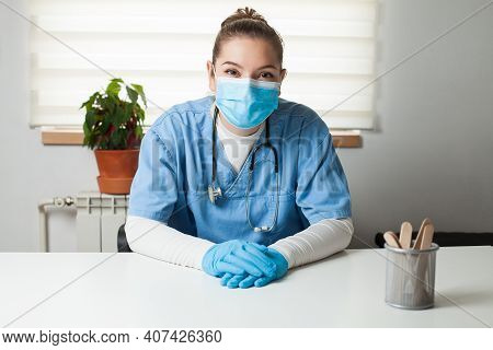 Young Female Caucasian General Practitioner Sitting By Her Desk In Office,wearing Blue Uniform,prote