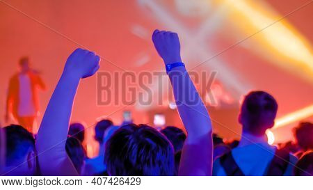 Teenage Boy Partying, Cheering, Raising Hands Up At Rock Concert In Front Of Stage Of Nightclub - Ba
