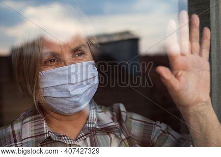 Portrait Of Elderly Senior Citizen Wearing Face Mask Looking Through Room Window,coronavirus Covid-1
