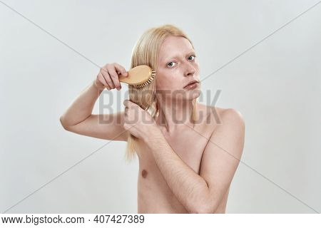 Young Caucasian Man Grooming His Long Blond Hair With Wooden Comb While Standing On White Background
