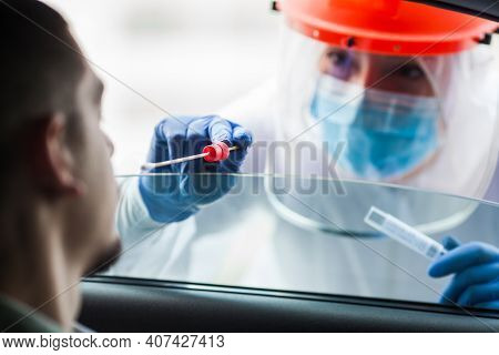Covid-19 Drive-thru Patient Specimen Collection,female Medical Worker Performing Nasal Swab On Young