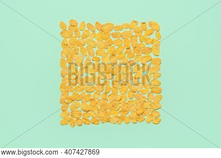 Flat Lay With A Bunch Of Corn Flakes Arranged In A Square On A Green Colored Background. Top View Wi
