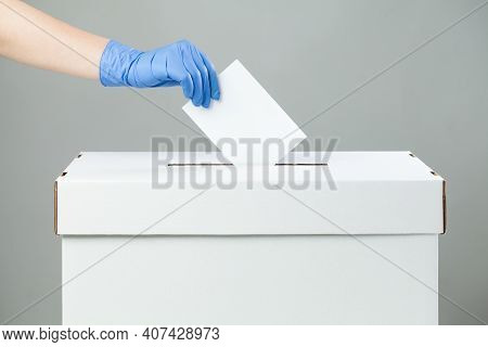 Caucasian Female Hand Wearing Blue Protective Latex Rubber Glove Placing Ballot Paper In Vote Box,si