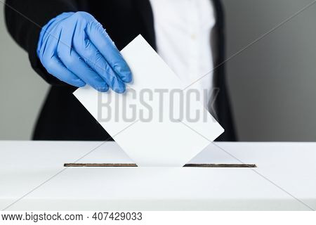 Person In Black Suit Wearing Blue Protective Latex Rubber Gloves Putting Ballot Paper In Vote Box, E